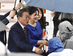 South Korean President Moon Jae-in, left, and his wife Kim Jung-sook are greeted on their arrival at Kansai International Airport in Izumisano, Osaka prefecture, western Japan, Thursday, June 27, 2019. Group of 20 leaders gather in Osaka on June 28 and 29 for their annual summit.(Nobuki Ito/Kyodo News via AP)