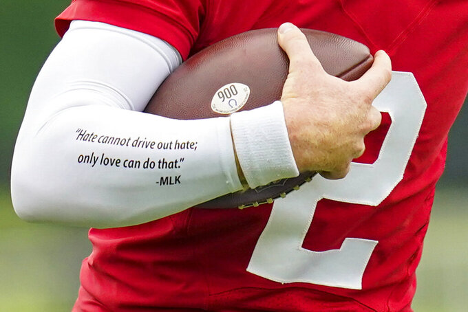Indianapolis Colts quarterback Carson Wentz wears a quote from Martin Luther King on his sleeve as runs a drill during practice at the NFL team's football training camp in Westfield, Ind., Wednesday, July 28, 2021. (AP Photo/Michael Conroy)