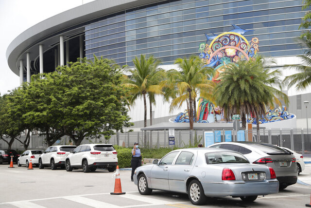 Vehicles pass by the home run sculpture as they wait in line outside of Marlins Park at a COVID-19 testing site during the coronavirus pandemic, Monday, July 6, 2020, in Miami. The long line of cars each morning as players arrive at work provides a reminder of the risks when they leave. Behavior away from the ballpark will be a big factor in determining whether Major League Baseball's attempt to salvage the 2020 season can succeed. (AP Photo/Lynne Sladky)