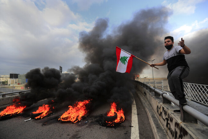 A protester waves a Lebanese flag near burning tires set to block a main highway, during a protest in the town of Jal el-Dib, north of Beirut, Lebanon, Monday, March 8, 2021. The dayslong protests intensified Monday amid a crash in the local currency, increase of consumer goods prices and political bickering between rival groups that has delayed the formation of a new government. (AP Photo/Hussein Malla)