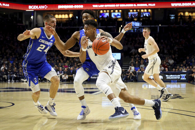Xavier guard Paul Scruggs (1) drives to the basket as Creighton guard Ty-Shon Alexander (5) and guard Mitch Ballock (24) defend in the first half of an NCAA college basketball game Saturday, Jan. 11, 2020, in Cincinnati. (Kareem Elgazzar/The Cincinnati Enquirer via AP)