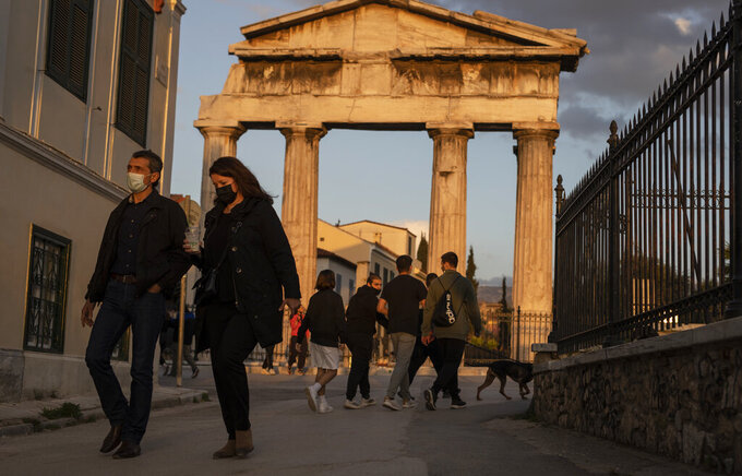 People wearing protective face masks walk in front the Gate of the ancient Roman agora, in Plaka, district of Athens, on Tuesday, April 6, 2021. Lockdown measures have been in force since early November but an ongoing surge in COVID-19 infections remains high as the country battles to emerge from deep recession. (AP Photo/Petros Giannakouris)