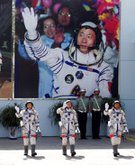 FILE - In this June 16, 2012 file photo, Chinese astronauts from left, Liu Yang, Jing Haipeng and Liu Wang wave and walk before a giant portrait of China's first astronaut Yang Liwei, as they depart for the Shenzhou 9 spacecraft rocket launch pad at the Jiuquan Satellite Launch Center in Jiuquan, China. China's landing of its third probe on the moon is part of an increasingly ambitious space program that has a robot rover en route to Mars, is developing a reusable space plane and plans to put humans back on the lunar surface. (AP Photo/Ng Han Guan, File)