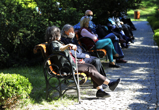 People wearing face masks for protection against the coronavirus, sit in a public garden in Ankara, Turkey, Sunday, May 24, 2020, during a four-day curfew declared by the government in an attempt to control the spread of coronavirus. Turkey's senior citizens were allowed to leave their homes for a third time as the country continues to ease some coronavirus restrictions. (AP Photo/Burhan Ozbilici)