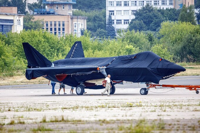 Hidden under tarpaulin, a prospective Russian fighter jet is being towed to a parking spot before its presentation at the Moscow international air show in Zhukovsky outside Moscow, Russia, Thursday, July 15, 2021. Russian aircraft makers say they will present a prospective new fighter jet at a Moscow air show that opens next week. The new warplane hidden under tarpaulin was photographed being towed to a parking spot across the airfield in Zhukovsky outside Moscow. That's where MAKS-2021 International Aviation and Space Salon opens on Tuesday. Russian President Vladimir Putin is set to visit the show's opening. (AP Photo/Ivan Novikov-Dvinsky)