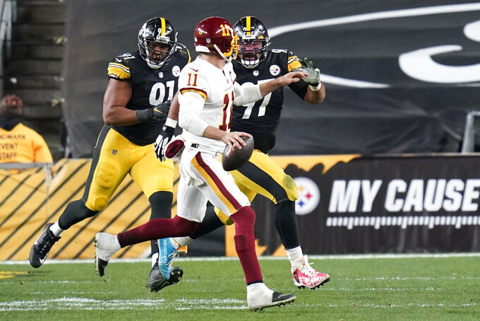 Washington Football Team quarterback Alex Smith (11) looks to pass with Pittsburgh Steelers defensive ends Cameron Heyward (97) and Stephon Tuitt (91) defending during the second half of an NFL football game, Monday, Dec. 7, 2020, in Pittsburgh. (AP Photo/Keith Srakocic)