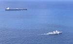 In this undated photo released by Indonesian Maritime Security Agency (BAKAMLA), a BAKAMLA ship escorts Iranian-flagged tanker MT Horse, top left, as they sail towards Batam Island, Indonesia. Indonesian authorities detained the crews MT Horse and Panamanian-flagged MT Freya that were seized Sunday for illegally transferring oil in Indonesian waters, an official said Tuesday. (Indonesian Maritime Security Agency via AP)