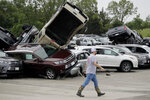 A worker walks past tornado-damaged Toyotas at a dealership in Jefferson City, Mo., Thursday, May 23, 2019, after a tornado tore though late Wednesday. (AP Photo/Charlie Riedel)