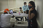 A man speaks with his mother who has been admitted in a COVID-19 hospital through a video phone facility by the COVID help desk, as another leaves crying after talking to her relative, outside a hospital, in New Delhi, India, Friday, July 3, 2020. India's number of coronavirus cases passed 600,000 on Thursday with the nation's infection curve rising and its testing capacity being increased. More than 60% of the cases are in the worst-hit Maharashtra state, Tamil Nadu state, and the capital territory of New Delhi. (AP Photo/Manish Swarup)