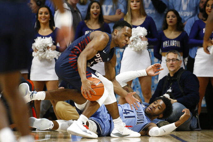 Pennsylvania's Jordan Dingle, left, grabs a loose ball next to Villanova's Saddiq Bey during the first half of an NCAA college basketball game Wednesday, Dec. 4, 2019, in Villanova, Pa. (AP Photo/Matt Slocum)