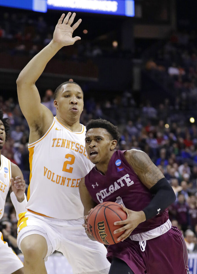 Colgate's Jordan Burns, right, drives past Tennessee's Grant Williams in the second half during a first-round game in the NCAA men's college basketball tournament in Columbus, Ohio, Friday, March 22, 2019. Tennessee won 77-70. (AP Photo/Tony Dejak)