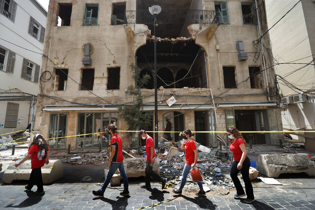 University students who volunteered to help clean damaged homes and give other assistance, pass in front of a building that was damaged by last week's explosion, in Beirut, Lebanon, Tuesday, Aug. 11, 2020. The explosion that tore through Beirut left around a quarter of a million people with homes unfit to live in. But there are no collective shelters, or people sleeping in public parks. That's because in the absence of the state, residents of Beirut opened their homes to relatives, friends and neighbors. (AP Photo/Hussein Malla)