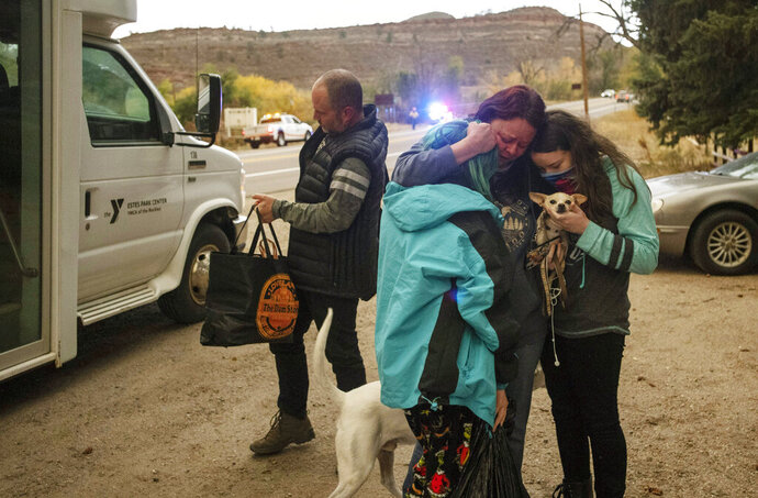 Melanie Luther embraces her two daughters Julie and Alex after reuniting with them and her husband Bryan Luther after all three were stranded in Estes Park when the city was evacuated due to the East Troublesome Fire, now the second largest in Colorado history, at The Dam Store along U.S. Highway 34 near Loveland, Colo., on Thursday, Oct. 22, 2020. (Bethany Baker/The Coloradoan via AP)