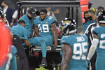 Teammates watch as Jacksonville Jaguars outside linebacker Leon Jacobs (48) is taken off the field after he was injured during the first half of an NFL football game against the Miami Dolphins, Thursday, Sept. 24, 2020, in Jacksonville, Fla. (AP Photo/Phelan M. Ebenhack)
