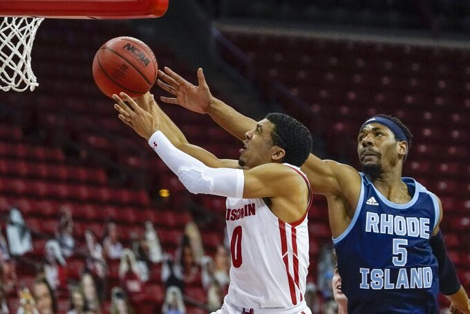 Wisconsin's D'Mitrik Trice drives past Rhode Island's Antwan Walker during the first half of an NCAA college basketball game Wednesday, Dec. 9, 2020, in Madison, Wis. (AP Photo/Morry Gash)