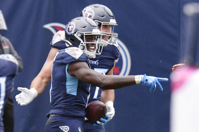 Tennessee Titans wide receiver A.J. Brown, front, celebrates after scoring a touchdown against the Houston Texans in the first half of an NFL football game Sunday, Oct. 18, 2020, in Nashville, Tenn. (AP Photo/Mark Zaleski)