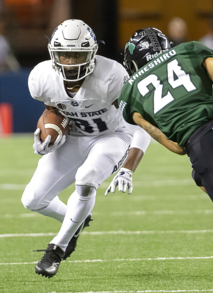 Utah State wide receiver Savon Scarver (81) attempts to get past Hawaii defensive back Kai Kaneshiro (24) in the first half of an NCAA college football game, Saturday, Nov. 3, 2018, in Honolulu. (AP Photo/Eugene Tanner)