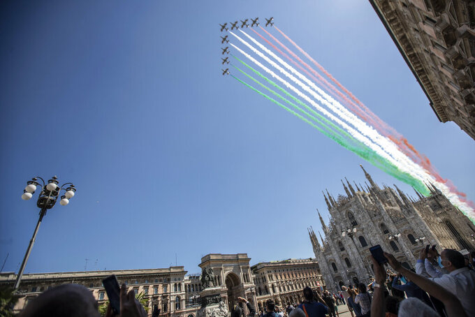 People gather to look at the Frecce Tricolori aerobatic squad of the Italian Air Force fly over Milan's Duomo cathedral, northern Italy, Monday, May 25, 2020 on the occasion of the 74th anniversary of the founding of the Italian Republic on June 2, 1946. This year the acrobatic squad will fly over several Italian cities to bring a message of unity and solidarity during the coronavirus pandemic.(AP Photo/Luca Bruno)