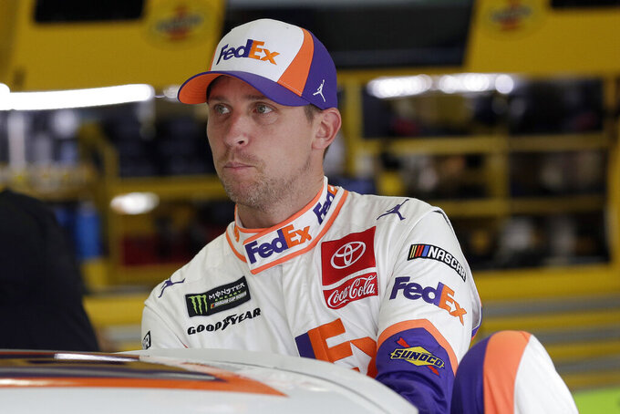 Denny Hamlin climbs into is car to practice for Sunday's NASCAR Cup Series auto race at Charlotte Motor Speedway in Concord, N.C., Saturday, Sept. 28, 2019. (AP Photo/Gerry Broome)