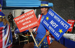 Anti Brexit campaigner Steve Bray holds banners outside the entrance to the Labour Party Conference at the Brighton Centre in Brighton, England, Monday, Sept. 23, 2019. (AP Photo/Kirsty Wigglesworth)