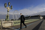 A man wearing a face mask walks past the London Eye on Westminster Bridge in London, Friday, Oct. 16, 2020. The British government is sticking to its strategy of tiered, regional restrictions to combat COVID-19 amid mounting political and scientific pressure for stronger nationwide measures to prevent the pandemic from spiraling out of control. (AP Photo/Kirsty Wigglesworth)