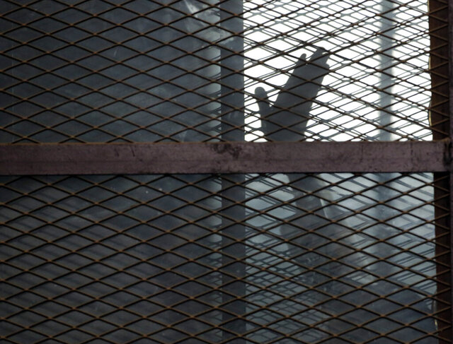FILE - In this Aug. 22, 2015 file photo, a Muslim Brotherhood member waves his hand from a defendants cage in a courtroom in Torah prison, southern Cairo, Egypt. In some cells in Iran, Egypt, Syria and other countries in the Middle East, prisoners are crammed in by the dozens, with little access to hygiene or medical care. So if one infection gets in, the novel coronavirus could run rampant. (AP Photo/Amr Nabil, File)