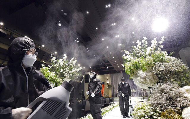 People wearing protective gear disinfect as a precaution against the new coronavirus at a wedding hall in Suwon, South Korea, Tuesday, June 2, 2020. (Kim Jong-taik/Newsis via AP)