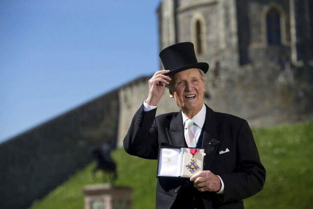 "FILE - In this April 15, 2014 file photo, Nicholas Parsons poses for the media with his Commander of the Order of the British Empire (CBE) medal given to him by Britain's Queen Elizabeth at Windsor Castle, Berkshire. British broadcaster Nicholas Parsons, who hosted the witty, wordy radio program ""Just a Minute"" for more than 50 years, has died at the age of 96. Parson's agent, Jean Diamond, said he died Tuesday, Jan. 28, 2020 morning after a short illness. (Steve Parsons/PA via AP, file)"