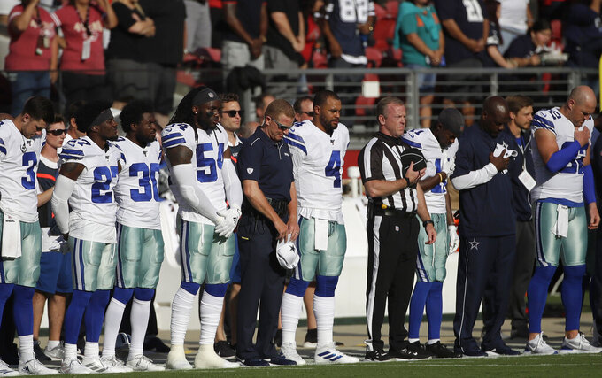 Dallas Cowboys coach Jason Garrett, center, stands next to quarterback Dak Prescott (4) as they observe a moment of silence for victims of the shootings in Gilroy, Calif.; El Paso, Texas; and Dayton, Ohio, before an NFL preseason football game between the San Francisco 49ers and the Cowboys in Santa Clara, Calif., Saturday, Aug. 10, 2019. (AP Photo/Jeff Chiu)