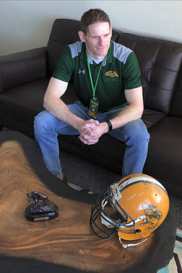 In this Tuesday, Jan. 7, 2020 photo, former North Dakota State all-American linebacker Sean Fredricks poses in Fargo, N.D., with his Bison Hall of Fame plaque, football helmet and lanyard showing his membership in the Bison Football Players Association. Fredricks, an attorney, is president of the 3-year-old association, which has been raising thousands of dollars to donate to worthy causes such as families of deceased players, a Christmas toy drive and for the recovery of a rival player who was paralyzed in a skiing accident. (AP Photo/Dave Kolpack)