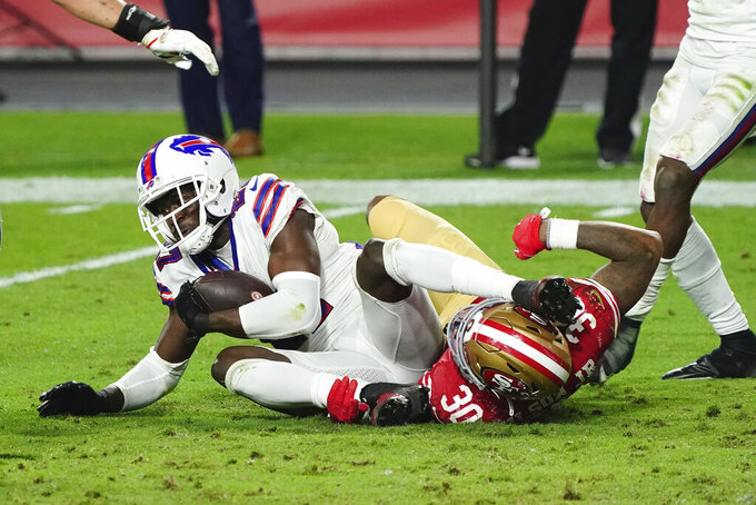 Buffalo Bills cornerback Tre'Davious White is hit by San Francisco 49ers running back Jeff Wilson (30) after White intercepted a pass during the second half of an NFL football game, Monday, Dec. 7, 2020, in Glendale, Ariz. (AP Photo/Rick Scuteri)