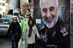 FILE - In this Jan. 9, 2020, file photo, women walk past a banner of Iranian Revolutionary Guard Gen. Qassem Soleimani, who was killed in Iraq in a U.S. drone attack, in Tehran, Iran. Iran has had its fingers in Iraq's politics for years, but the U.S. killing of an Iranian general and Iraqi militia commander outside Baghdad has added new impetus to the effort, stoking anti-Americanism that Tehran now hopes it can exploit to help realize the goal of getting U.S. troops out of the country. (AP Photo/Vahid Salemi, File)