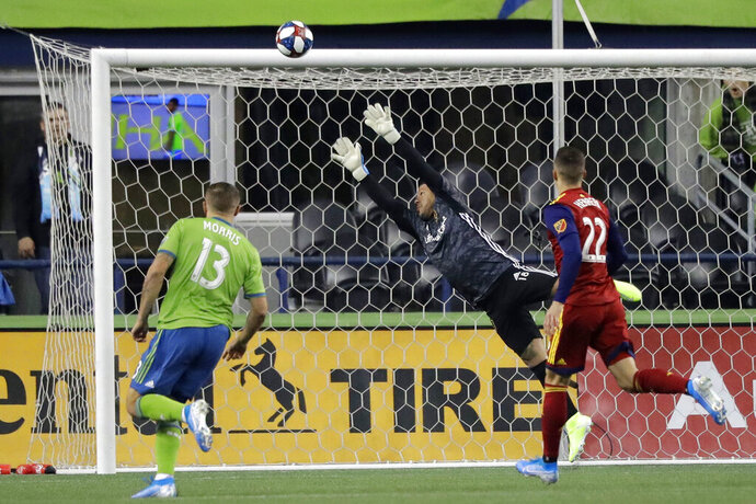 Real Salt Lake goalkeeper Nick Rimando, center, leaps as a shot goes wide and Seattle Sounders forward Jordan Morris, left, and Real Salt Lake defender Aaron Herrera, right, watch during the first half of an MLS Western Conference semifinal playoff soccer match Wednesday, Oct. 23, 2019, in Seattle. (AP Photo/Ted S. Warren)