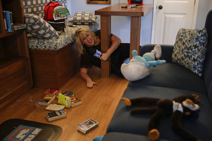 TV reporter Wendy Burch takes cover under a table in a Big Shaker simulating a 6.8 magnitude earthquake Thursday, Oct. 18, 2018, in Los Angeles. Millions of people around the world are practicing the basic earthquake safety skill of