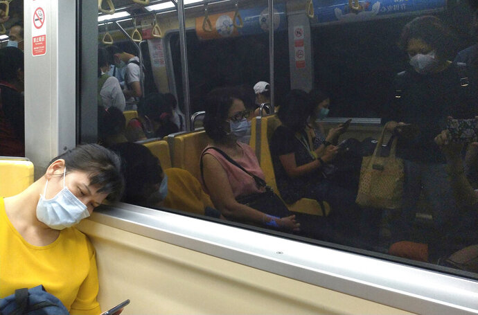 People riding the subway wear face masks to protect against the spread of the coronavirus in Taipei, Taiwan, Thursday, July 30, 2020. (AP Photo/Chiang Ying-ying)
