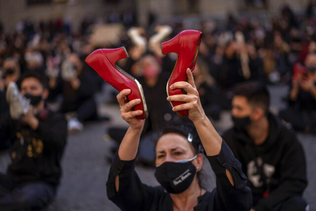 A flamenco dancer holds up her dancing shoes during a protest organised by dance associations against virus restrictions, in Barcelona, Monday, Nov. 9, 2020, as Spain continue with new measures to try to prevent the spread of COVID-19. (AP Photo/Emilio Morenatti)