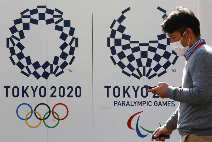 A man walks by logos of the Tokyo Olympic and Paralympic Games in Tokyo, Monday, Feb. 1, 2021. Pressure is building on Japanese organizers and the IOC to explain exactly how they plan to hold the Tokyo Olympics in the midst of a pandemic. (AP Photo/Koji Sasahara)