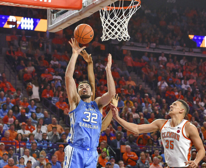 North Carolina's Luke Maye (32) shoots while defended by Clemson's Javan White (35) and another player during the second half of an NCAA college basketball game Saturday, March 2, 2019, in Clemson, S.C. (AP Photo/Richard Shiro)
