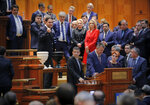 An opposition lawmaker clenches his fist after voting as Romanian Prime Minister Viorica Dancila watches along with government members of a no confidence vote in Bucharest, Romania, Thursday, Oct. 10, 2019. Romania's Social Democrat government has lost a vote of no-confidence in Parliament. (AP Photo/Vadim Ghirda)