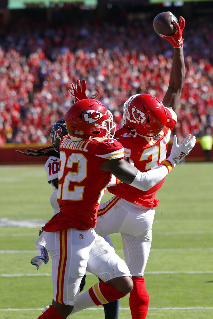 Kansas City Chiefs cornerback Charvarius Ward (35) intercepts a pass intended for Houston Texans wide receiver DeAndre Hopkins (10) with Chiefs safety Juan Thornhill (22) watching during the second half of an NFL football game in Kansas City, Mo., Sunday, Oct. 13, 2019. (AP Photo/Colin E. Braley)
