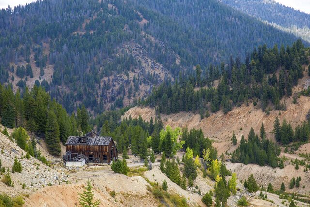 This Sept. 19, 2018 photo shows the last standing building above the Yellow Pine Pit open-pit gold mine in the Stibnite Mining District in central Idaho, where a company hopes to start mining again. Documents show the Trump administration intervening in a U.S. Forest Service decision so that a Canadian company could write a key environmental report on its proposed open-pit gold mines in central Idaho. (Riley Bunch/Idaho Press-Tribune via AP)