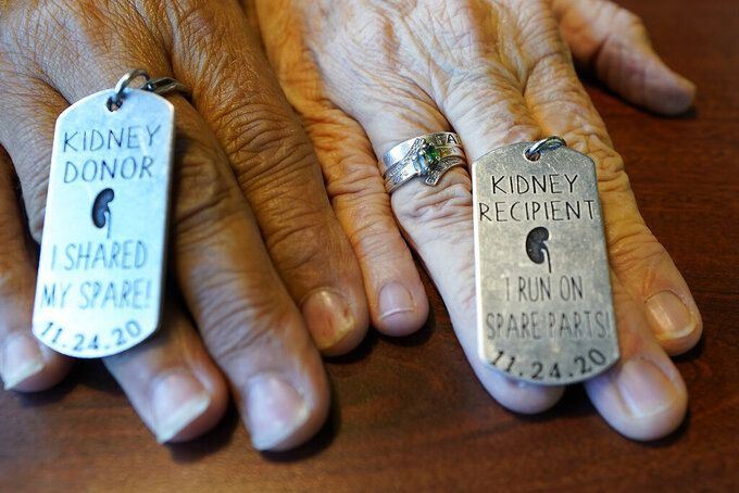 Debby-Neal Stricland and Mylaen Merthe show off donor/recipient tags they had made during a get together Tuesday, May 25, 2021, at a restaurant in Ocala, Fla. Debby now married to Jim Strickland donated a kidney to Mylaen Merthe, Jim's ex-wife. (AP Photo/John Raoux)