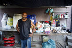 In this Nov. 27, 2019 photo, Marcelin Saingiles, a store owner who sells everything ranging from cold drinks to cookies, stands in his store in Delmas, a district of in Port-au-Prince, Haiti. The 39-year-old father of three children says that he now struggles to buy milk and vegetables. (AP Photo/Dieu Nalio Chery)