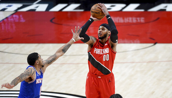 Portland Trail Blazers forward Carmelo Anthony, right, hits a shot over New York Knicks forward Obi Toppin, left, during the first half of an NBA basketball game in Portland, Ore., Sunday, Jan. 24, 2021. (AP Photo/Steve Dykes)