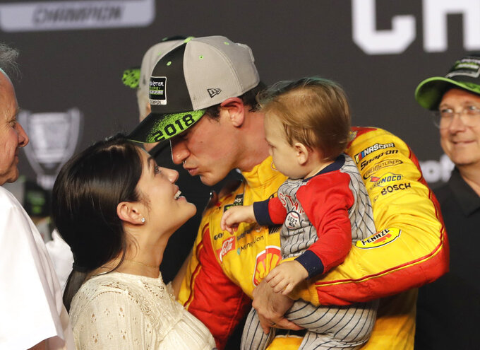 Joey Logano kisses his wife Brittany Baca, holding their son Hudson, after winning the NASCAR Cup Series Championship auto race at the Homestead-Miami Speedway, Sunday, Nov. 18, 2018, in Homestead, Fla. (AP Photo/Lynne Sladky)