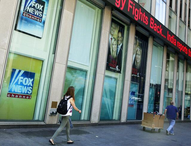 FILE- People pass the News Corporation headquarters building and Fox News studios in New York on Aug. 1, 2017. Several Fox News Channel executives and on-air personalities were exposed last week to a person on a private plane who later tested positive for COVID-19. It has led to some restrictions at the network. Anchor Bret Baier said Monday that he's tested negative three times in the wake of the flight and will be doing his nightly news show from home this week. (AP Photo/Richard Drew, File)