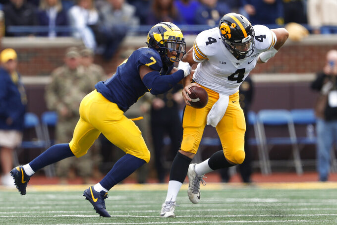Iowa quarterback Nate Stanley (4) breaks free from pressure by Michigan linebacker Khaleke Hudson (7) during the second half of an NCAA college football game in Ann Arbor, Mich., Saturday, Oct. 5, 2019. (AP Photo/Paul Sancya)