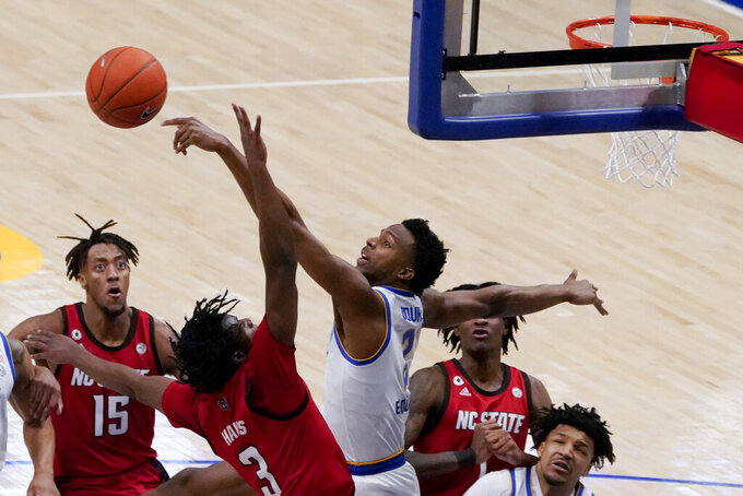 Pittsburgh's Femi Odukale (2) blocks a shot by North Carolina State's Cam Hayes (3) during the first half of an NCAA college basketball game, Wednesday, Feb. 17, 2021, in Pittsburgh. (AP Photo/Keith Srakocic)