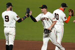 San Francisco Giants' Brandon Belt, left, celebrates with Alex Dickerson and Evan Longoria, right, after the Giants defeated the Colorado Rockies 5-2 in a baseball game in San Francisco, Tuesday, Sept. 22, 2020. (AP Photo/Jeff Chiu)
