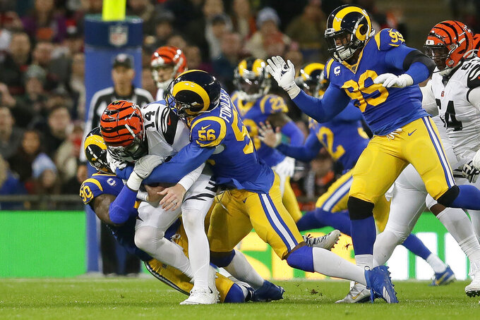 Cincinnati Bengals quarterback Andy Dalton (14) is sacked by Los Angeles Rams defensive end Michael Brockers (90) and defensive end Dante Fowler (56) during the first half of an NFL football game, Sunday, Oct. 27, 2019, at Wembley Stadium in London. (AP Photo/Tim Ireland)